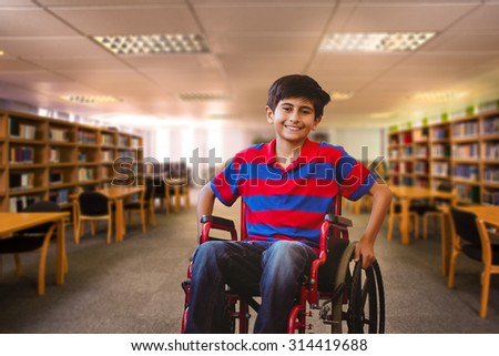 Boy sitting in wheelchair in school corridor against view of library - stock photo