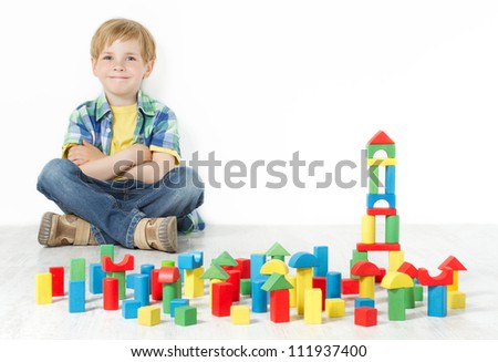 Boy sitting next to construction blocks and smiling - stock photo
