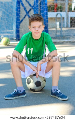 Boy sitting on a  ball in city sport playground