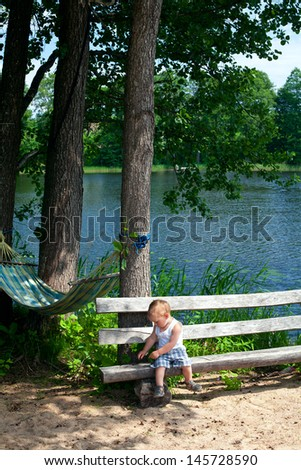 boy sitting on a bench next to the lake
