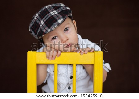 Boy, sitting on a chair - stock photo
