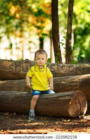 boy sitting on a log