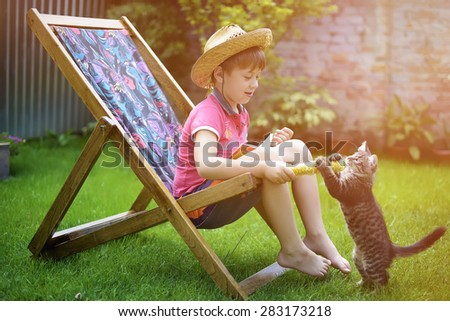 boy sitting on a lounge chair and playing with a cat - stock photo
