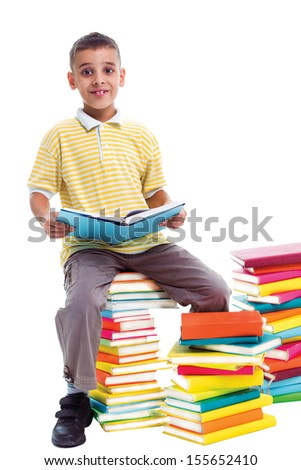 boy sitting on a pile of books and holding one book in his hands