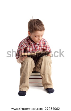 Boy sitting on a pile of books reads the book - stock photo