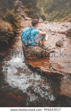 Boy sitting on a rock on mountain trail