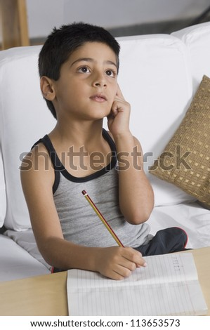 Boy sitting on a sofa and thinking