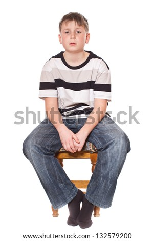 boy sitting on a stool on a white background - stock photo