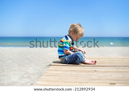 Boy sitting on a wooden walkway on the beach - stock photo