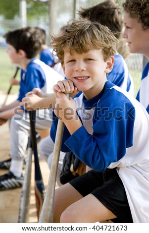 Boy sitting on bench with little league baseball team