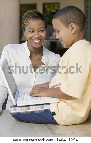 Boy sitting on counter and using laptop with happy mother in the living room - stock photo