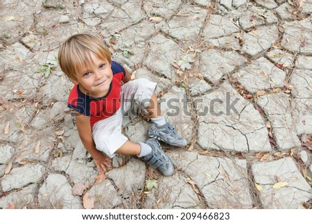 Boy sitting on dry ground and looking up.