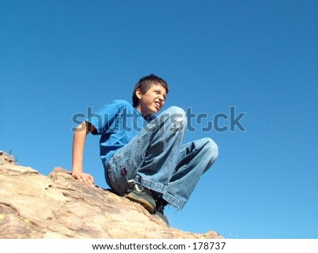 Boy sitting on rock against deep blue sky at Vasquez Rock, California - stock photo