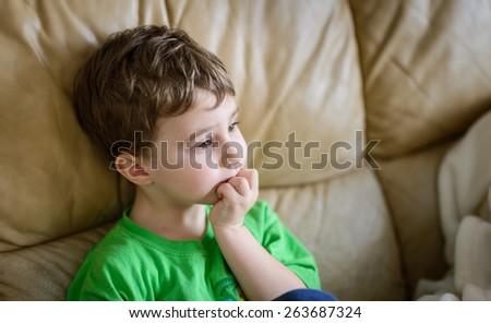 Boy sitting on sofa watching TV - stock photo