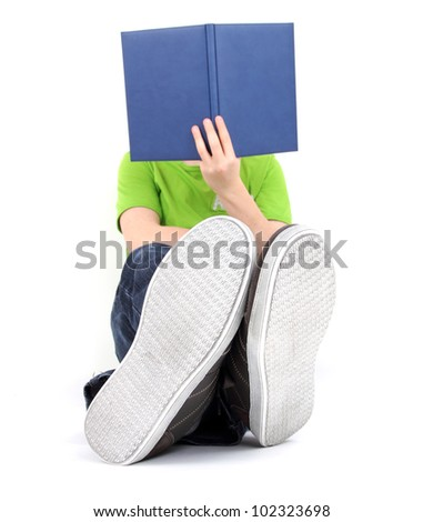 Boy sitting on the floor and reading a book - stock photo