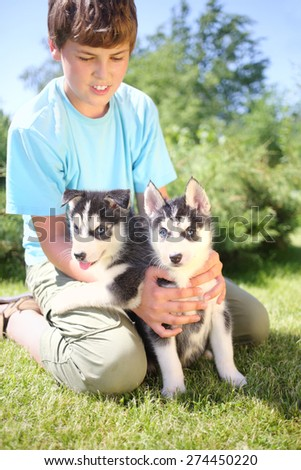 Boy sitting on the grass with two puppies husky - stock photo