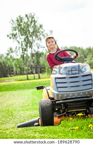 Boy sitting on the mower and cutting the grass - stock photo