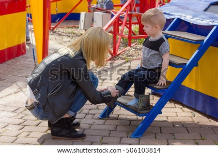 Boy sitting on the stairs and his mom is putting shoes on his legs