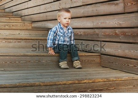 Boy sitting on the wood stairs - stock photo