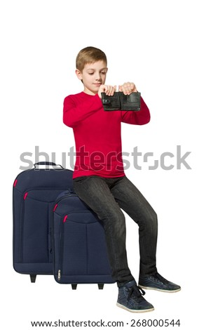 Boy sitting on travel bags holding empty wallet isolated on white