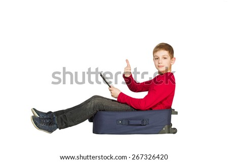 Boy sitting on travel bags holding tablet shoeing thumb up