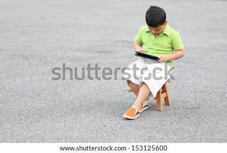 Boy sitting play a tablet on the road