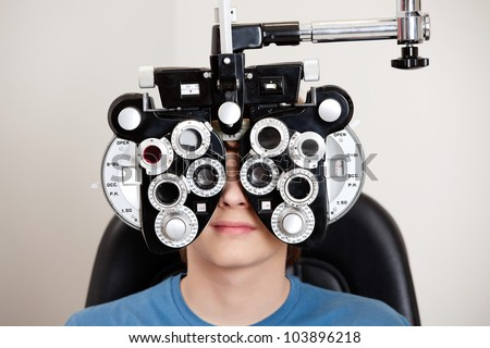 Boy sitting while undergoing an eye test with phoropter in the clinic - stock photo