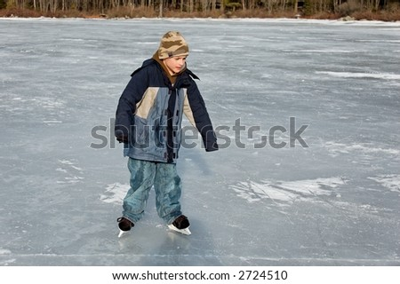 boy skating down lake without gloves - stock photo