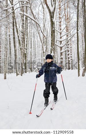 Boy ski running in winter forest looking sideways - stock photo