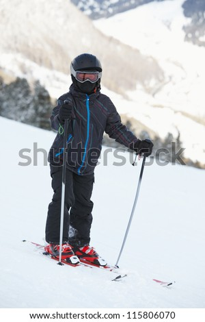 Boy skier in ski suit and helmet stands on snowy slope - stock photo