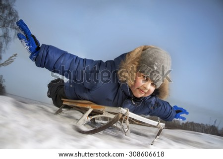 boy sledding with the mountains in the winter in the forest - stock photo