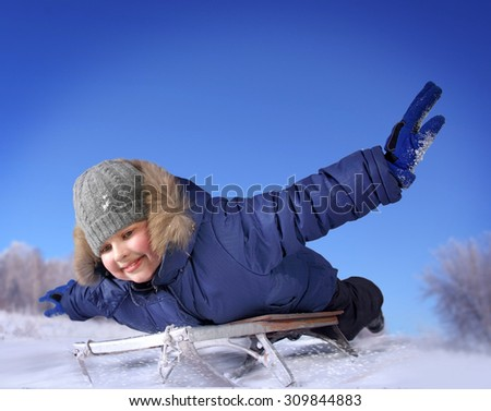 boy sledding with the mountains in the winter in the forest
