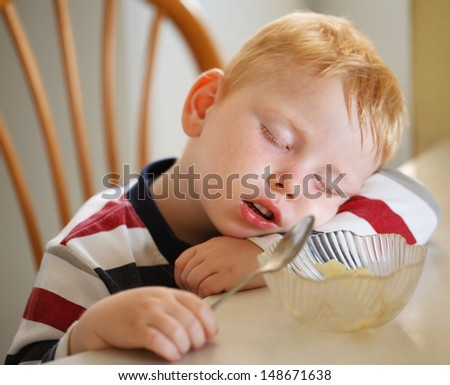 Boy sleeps with a spoon in his hand - stock photo