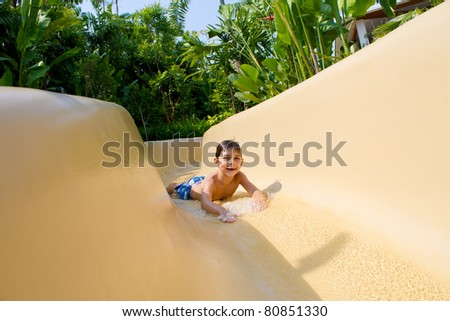 Boy Sliding Down Water Slide. - stock photo