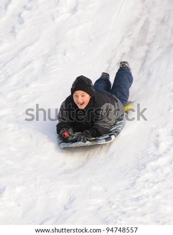 Boy sliding in the snow - stock photo