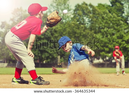 Boy sliding into base during a baseball game with Instagram style filter - stock photo