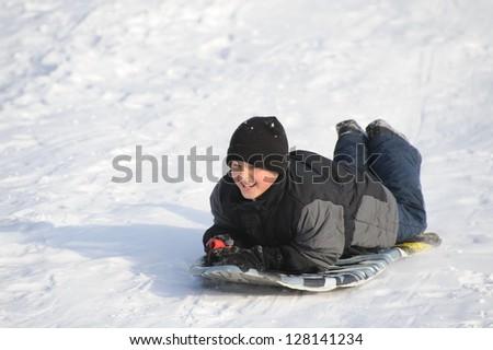 Boy sliding on the sled - stock photo