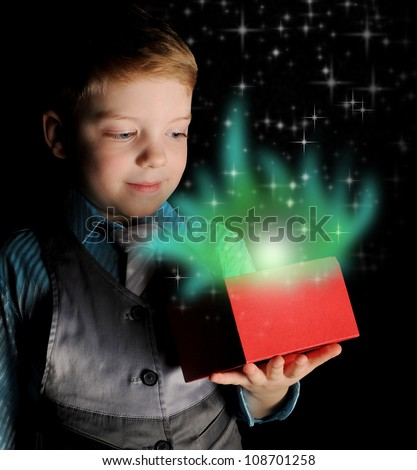 Boy smiles and holding a gift in magic packing on a black background - stock photo
