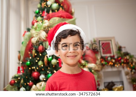 Boy smiles while wearing santa hat - stock photo