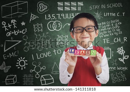 Boy smiling and holding LEARN crossword in class - stock photo