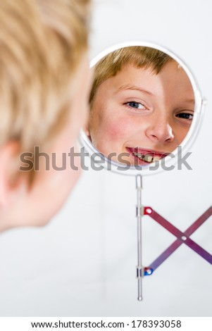 boy smiling and looking in a vanity mirror - stock photo
