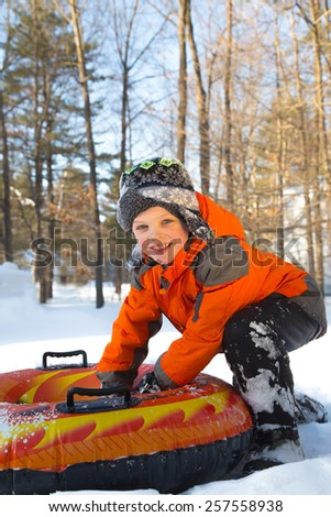 Boy snow tubing  - stock photo