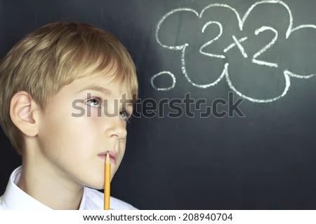 boy solves a mathematical task - stock photo