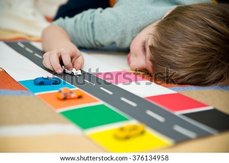 Boy sorting machines by color - stock photo