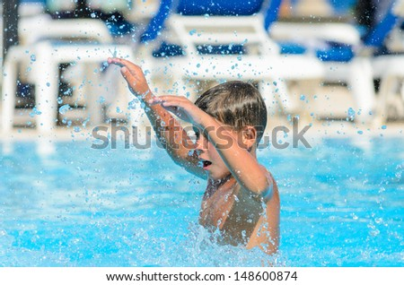 Boy splashes water in the pool.  - stock photo