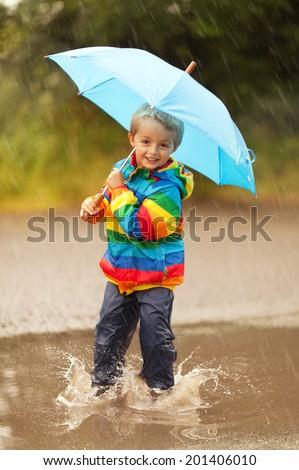 Boy splashing in puddle smiling holding a blue umbrella - stock photo