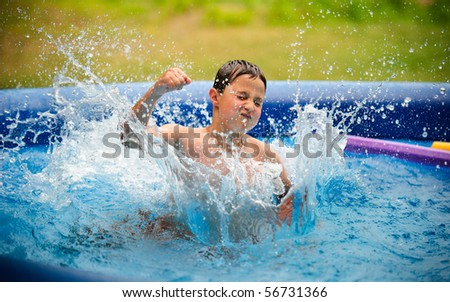 Boy splashing in the pool - stock photo