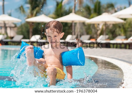 Boy splashing in the swimming pool - stock photo