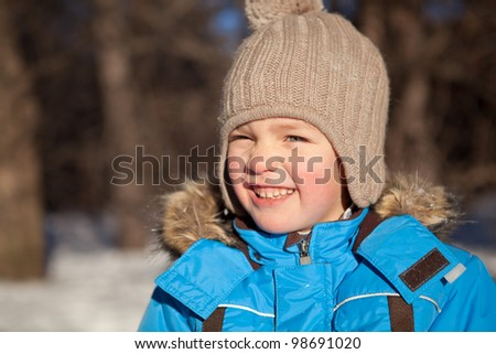 boy squinted at sun, winter, park - stock photo