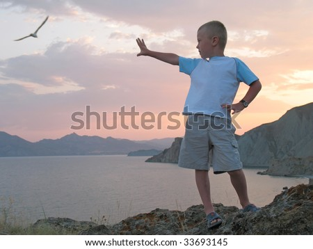 boy stand on mountain top at sunset